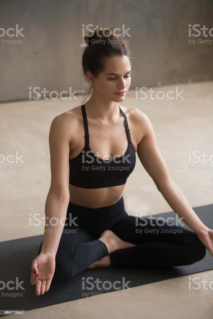 Young attractive woman sitting in Easy Seat pose, grey studio stock photo