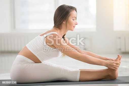 istock Young attractive woman sitting in paschimottanasana pose, white 663991336