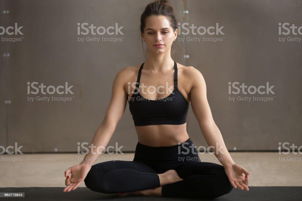 Young attractive woman sitting in Sukhasana pose, grey studio ba stock photo