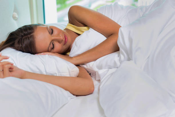Young attractive woman sleeping in bed at home stock photo