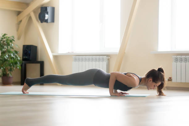 Young attractive woman standing in chaturanga dandasana pose, ho Young sporty happy woman practicing yoga, doing Push ups or press ups exercise, four limbed staff chaturanga dandasana pose, working out wearing grey sportswear, indoor full length, home or sport club namaskard geothermal area stock pictures, royalty-free photos & images