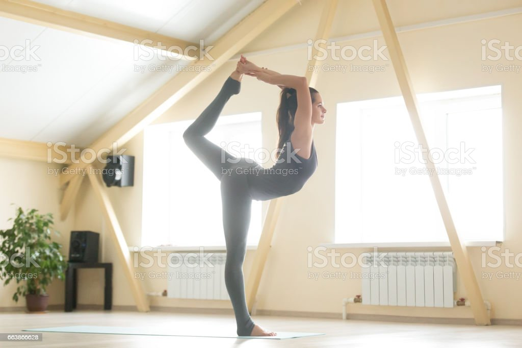 Young attractive woman standing in Natarajasana pose, home inter - foto de stock