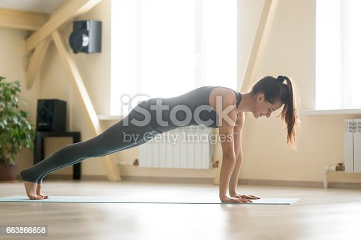 675173150 istock photo Young attractive woman standing in Plank pose, home interior bac 663866658