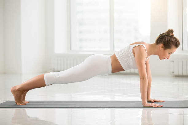 Young attractive woman standing in Plank pose, white color backg Young attractive yogi woman practicing yoga, doing Push ups or press ups exercise, standing in Plank pose, working out, wearing sportswear, sport bra, pants, indoor full length, white color background yogi stock pictures, royalty-free photos & images