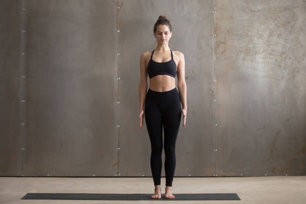 Young attractive woman standing in Tadasana pose, grey studio ba Young attractive yogi woman practicing yoga, standing in Tadasana exercise, mountain pose, working out, wearing black sportswear, cool urban style, full length, grey studio background namaskard geothermal area stock pictures, royalty-free photos & images