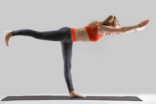 Young attractive woman standing in Warrior Three pose, grey stud Young attractive woman practicing yoga, standing in Warrior Three exercise, Virabhadrasana III pose, working out, wearing sportswear, red sports bra, pants, indoor full length, isolated, grey studio shoulder stand stock pictures, royalty-free photos & images