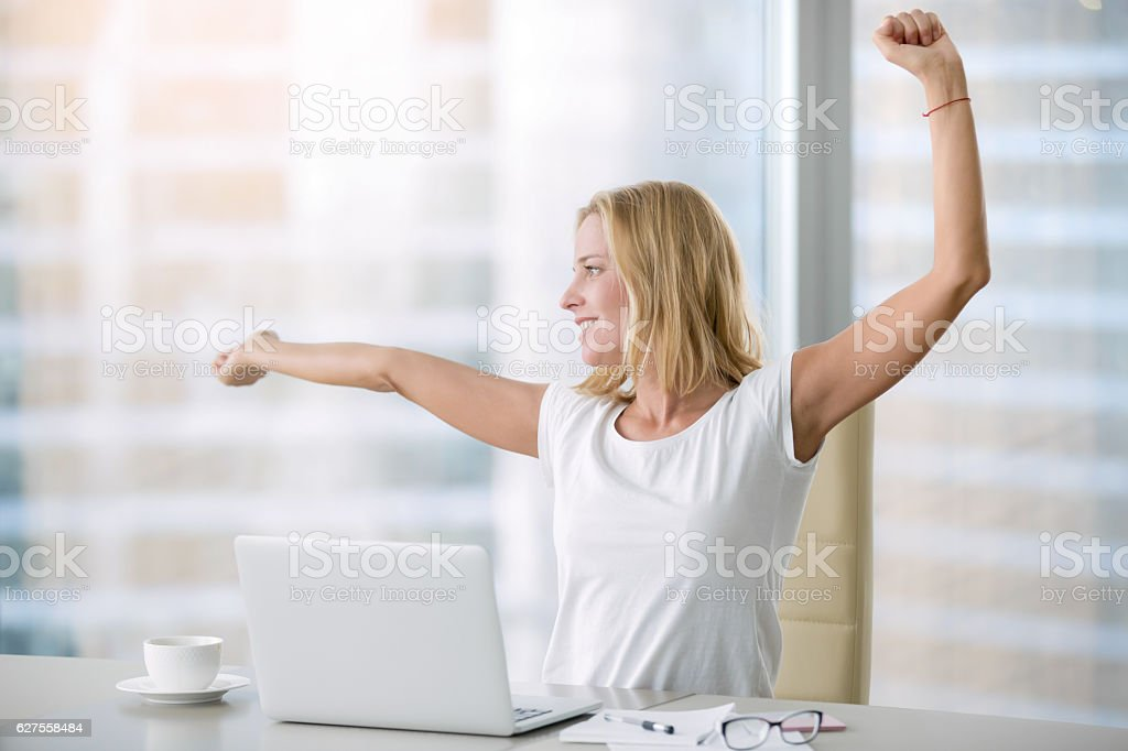 Young attractive woman at modern office desk, with laptop,...