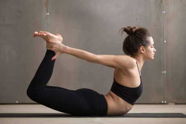 Young attractive woman stretching in Dhanurasana pose, grey stud stock photo