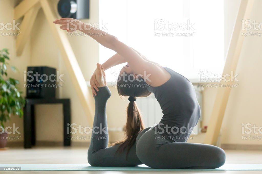 Young attractive woman stretching in Eka Pada Rajakapotasana pos stock photo