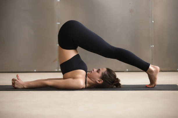 Young attractive woman stretching in Halasana pose, grey studio Young attractive woman practicing yoga, stretching in Halasana exercise, Plough pose, working out, wearing black sportswear, cool urban style, full length, grey studio background, side view shoulder stand stock pictures, royalty-free photos & images