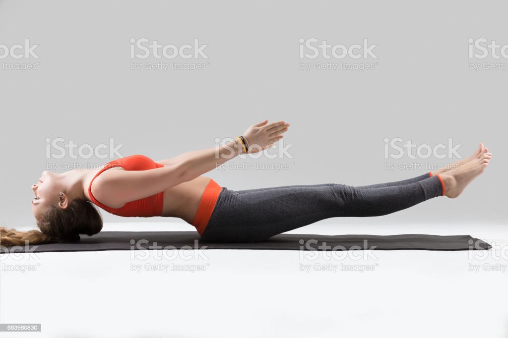 Young attractive woman stretching in Matsyasana pose, grey studi stock photo