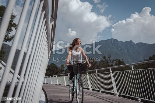 Young attractive woman with bicycle on a bridge surrounded by nature and architecture during a cloudy day