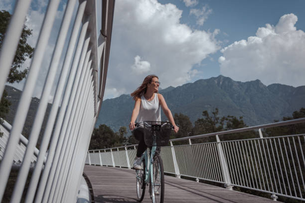 young attractive woman with bicycle on a bridge - all vocabulary foto e immagini stock
