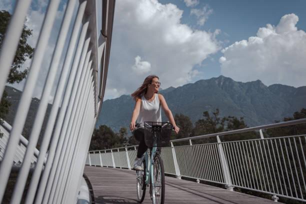 young attractive woman with bicycle on a bridge - all vocabulary zdjęcia i obrazy z banku zdjęć