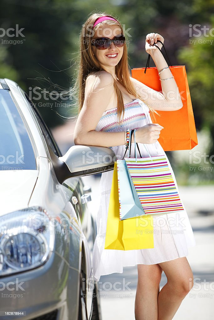 Young attractive woman with shopping bags standing by car royalty-free stock photo