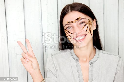 istock Young attractive woman with tiger colored tapes show