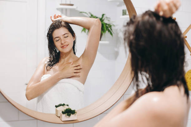 Young attractive woman with wet hair in white towel enjoying smooth skin after shaving armpits, reflection in mirror in stylish bathroom with greenery. Skin and body care. Hair Removal concept Young attractive woman with wet hair in white towel enjoying smooth skin after shaving armpits, reflection in mirror in stylish bathroom with greenery. Skin and body care. Hair Removal concept hair removal stock pictures, royalty-free photos & images, laser hair removal on face