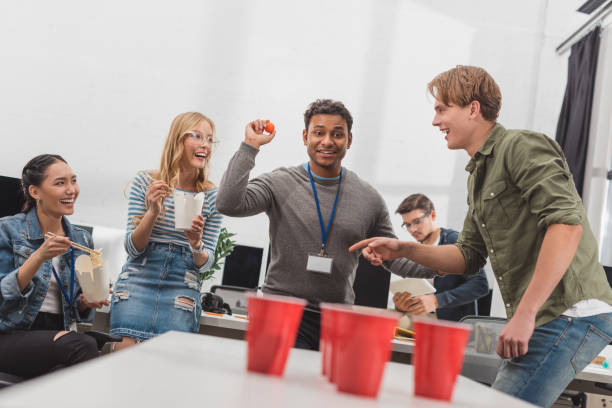 junge attraktive arbeitnehmer spielen bier pong im modernen büro nach der arbeit - lustige trinkspiele stock-fotos und bilder