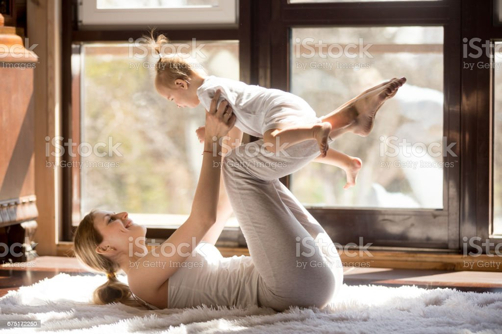 Young attractive yogi mother and baby daughter exercising at hom stock photo