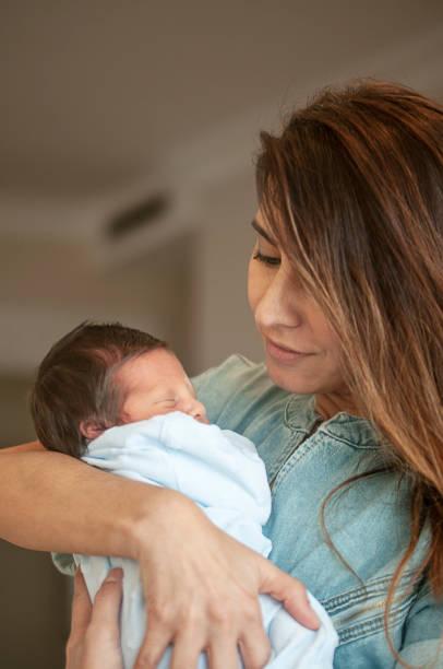 Junge Tante hält ihren neugeborenen Neffen fest – Foto