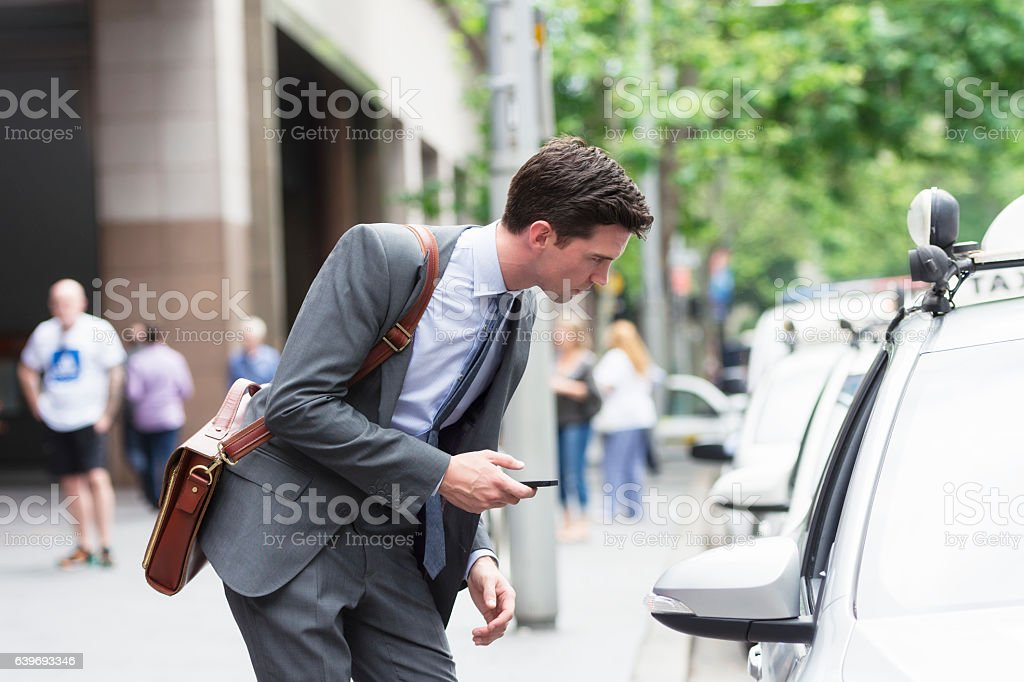 Young Australian business using taxi app stock photo