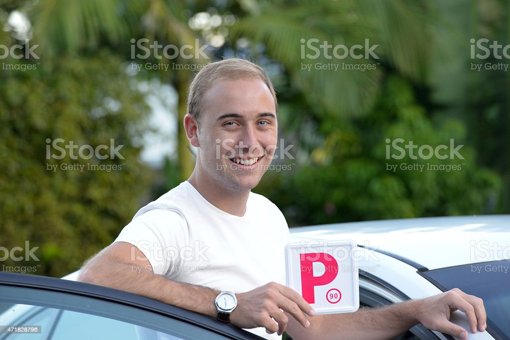 Young Australian male teenager learner driver holding a P plate stock photo