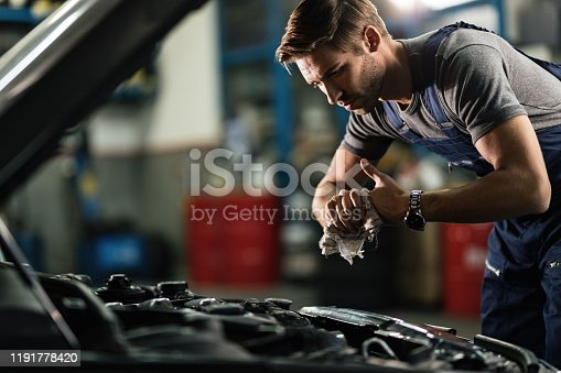 Young mechanic wiping his hands while repairing car engine in auto repair shop.