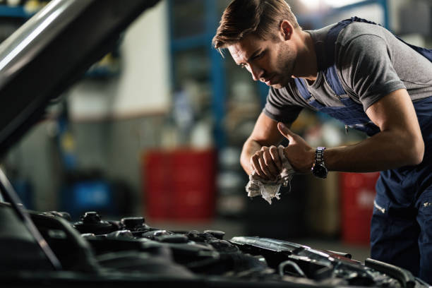 Young auto mechanic cleaning hands after working on car engine in a garage. Young mechanic wiping his hands while repairing car engine in auto repair shop. mechanic stock pictures, royalty-free photos & images