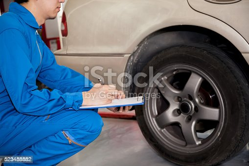 898487280 istock photo Young automotive technician checking on car tires in garage 523488882