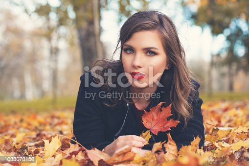 Young autumn woman lying on fall leaves outdoors, romantic portrait