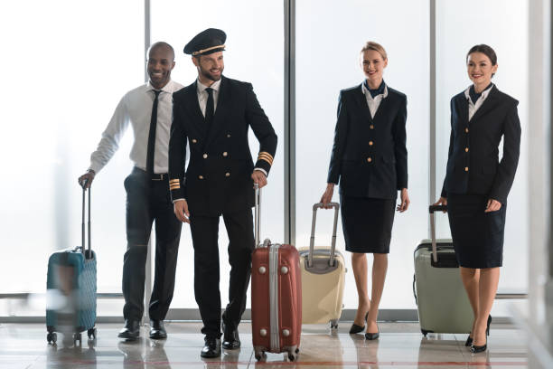 young aviation personnel team walking by airport loggy with suitcases young aviation personnel team walking by airport loggy with suitcases cabin crew stock pictures, royalty-free photos & images