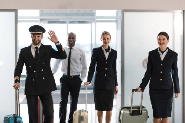 young aviation personnel team with suitcases at airport after flight stock photo
