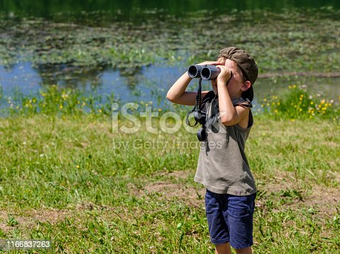 Child looking with binoculars at the wild nature in a mountain park