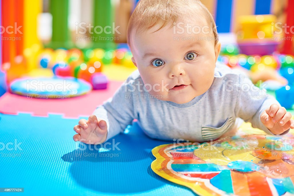 Young baby boy playing in his playpen doing tummy time stock photo