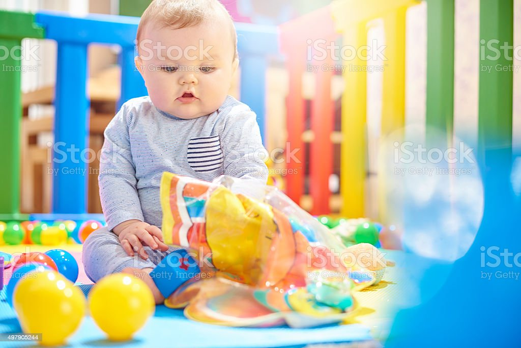 Young baby boy playing with his toys in playpen stock photo
