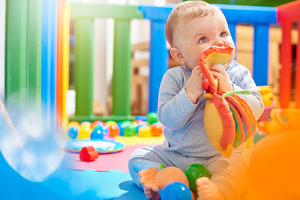 young baby boy playing with his toys in playpen - playpen stock pictures, royalty-free photos & images