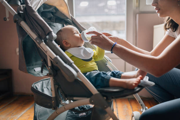 Young baby boy sitting in a stroller and drinking milk from a baby bottle stock photo