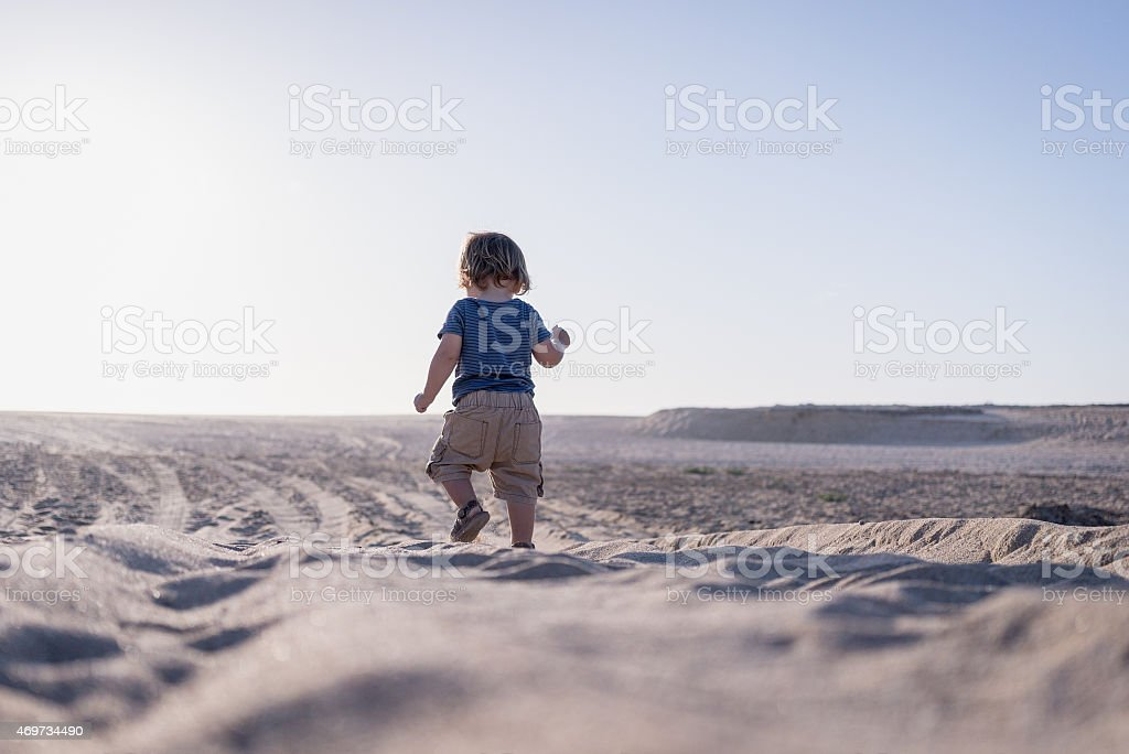Young baby boy walking on the beach stock photo