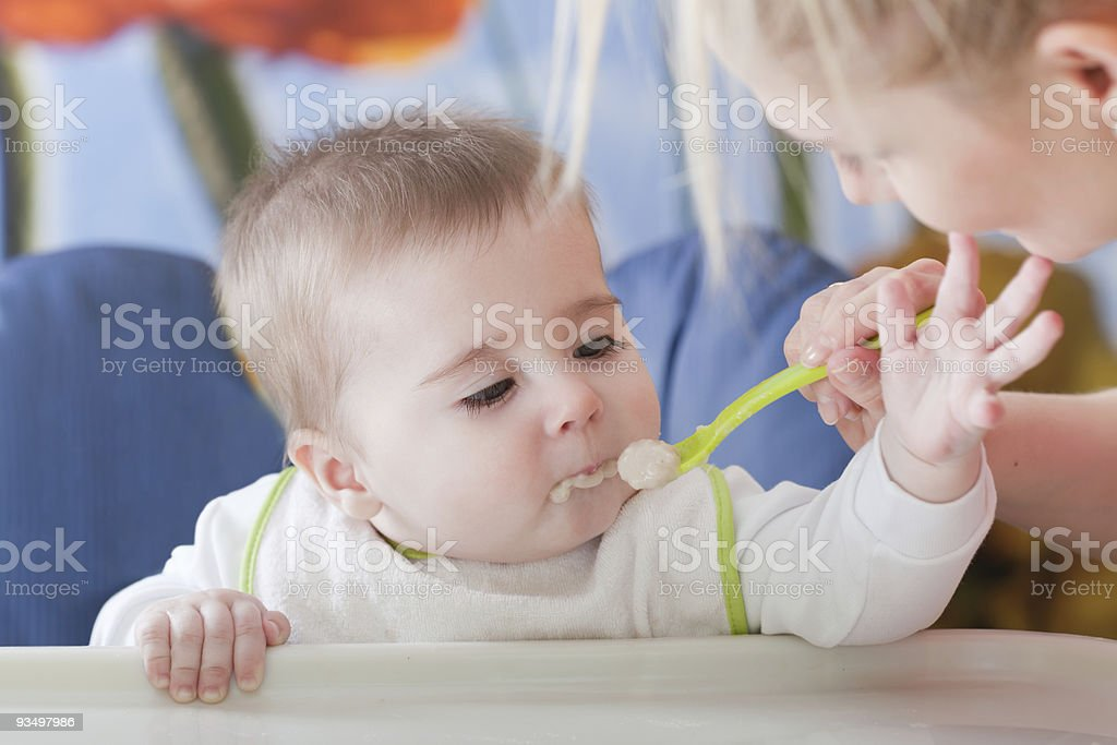 Young baby enjoying their first tastes of food stock photo