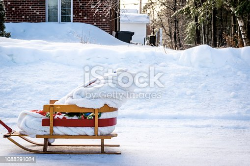 Young baby having a ride in a wooden sled with his grandmother by a cold day of winter in Quebec, Canada.