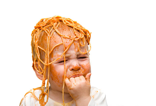 A young baby with spaghetti on their head and face stock photo