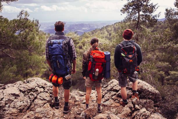 amigos mochileros jóvenes disfrutando de las vistas desde la cima de la montaña - mochilero fotografías e imágenes de stock