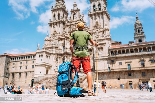 istock Young backpacker man pilgrim standing on the Obradeiro square (plaza) - the main square in Santiago de Compostela as a end of his Camino de Santiago pilgrimage. 1165361118