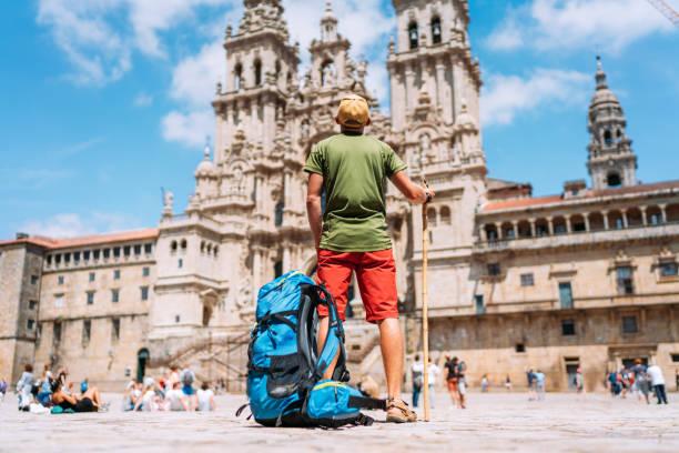 Joven mochilero peregrino de pie en la plaza del Obradeiro - la plaza principal de Santiago de Compostela como final de su peregrinación camino de Santiago. - foto de stock