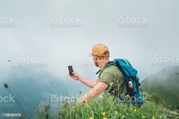 Photo of Young backpacker man taking picture of  cloudy valley bottom using smartphone during walking by the foggy cloudy weather mountain range .  Active sport backpacking healthy lifestyle concept.