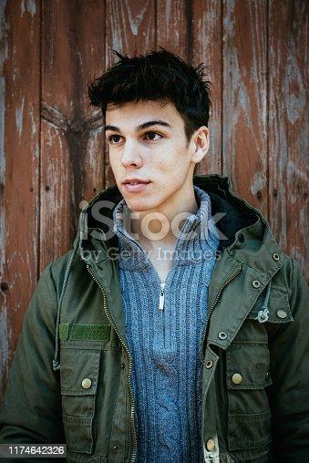 Portrait of a young trendy hiker in coat on old brown door