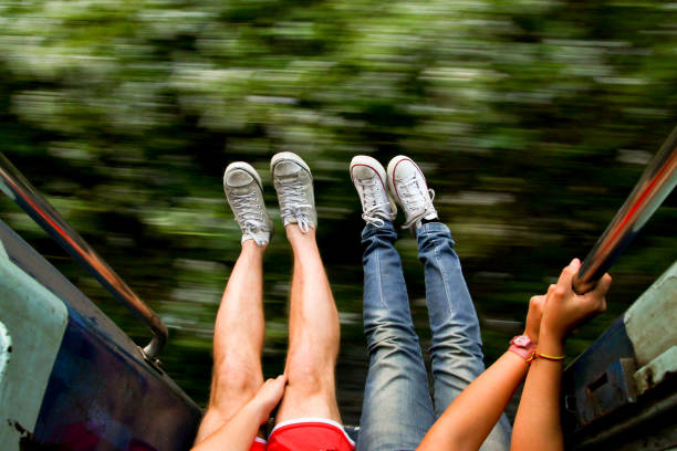 young backpackers couple traveling and living adveture trip exploring asia by train with legs out of fast moving train stock photo
