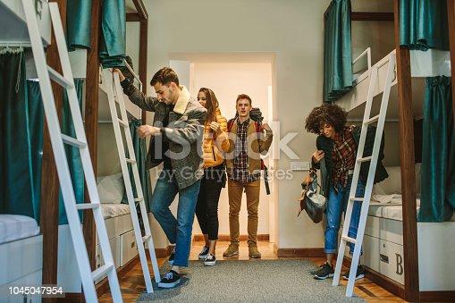 Young travelers in hostel bedroom.