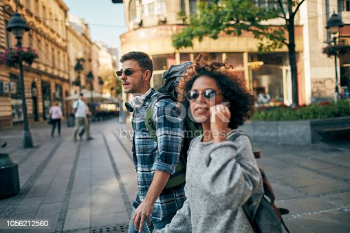 Young couple, Afro-American woman and Caucasian man exploring the city.