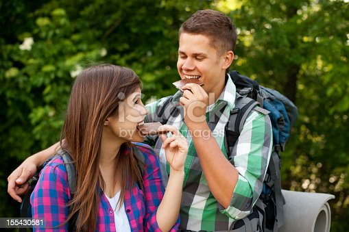 istock Young backpacking couple stopping for a snack of chocolate 155430581